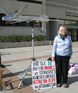 Ann Wright with sign that says: Our Tax $$ Pay for Drones at Syracuse Hancock Air Base, Destruction-Death in Afghanistan
